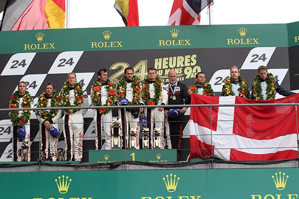 24-HEURES-DU-MANS-2013-Le-podium-GT-PRO-PORSCHE-92-1ere-DUMAS-LIEB-LIETZ-et-ASTON-DUMBRECKMUCKE-TURNER-QUI-BRANDISSENT-LE-DRAPEAU-DANOIS-en-Hommage-a-ALLAN-SIMONSEN-photo-Gilles-VITRY.j