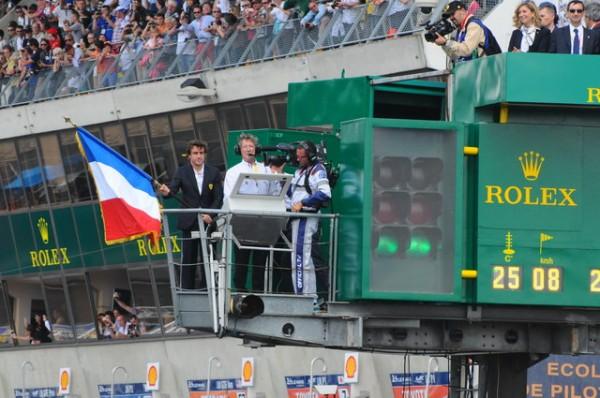 24-HEURES-DU-MANS-2014-Alonso-sur-la-passerelle-de-direction-de-course-avec-drapeau-Photo-Patrick-Martinoli.