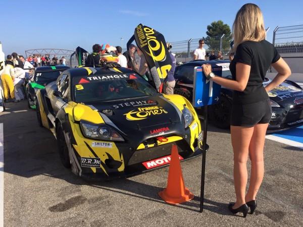 LAMERA-CUP-2015-Une-hotesse devant la voiture du Team ORHRES sur la-grille-de-depart et victorieuse dimanche en fin aprés midi.
