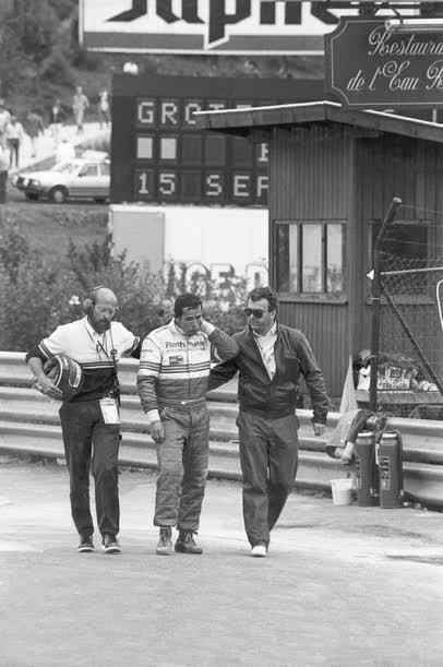 ICKX-choqué-après-laccident-mortel-de-Bellof-le-1er-septembre-1985-rejoint-son-stand-accompagné-dePeter-FALK-équipe-Porsche-et-dun-medecin©Manfred-GIET